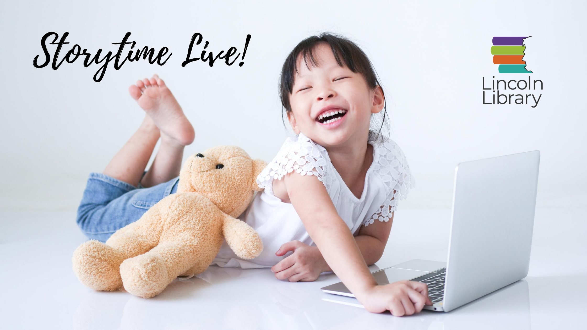 Young child laughing with teddy bear in front of a laptop computer