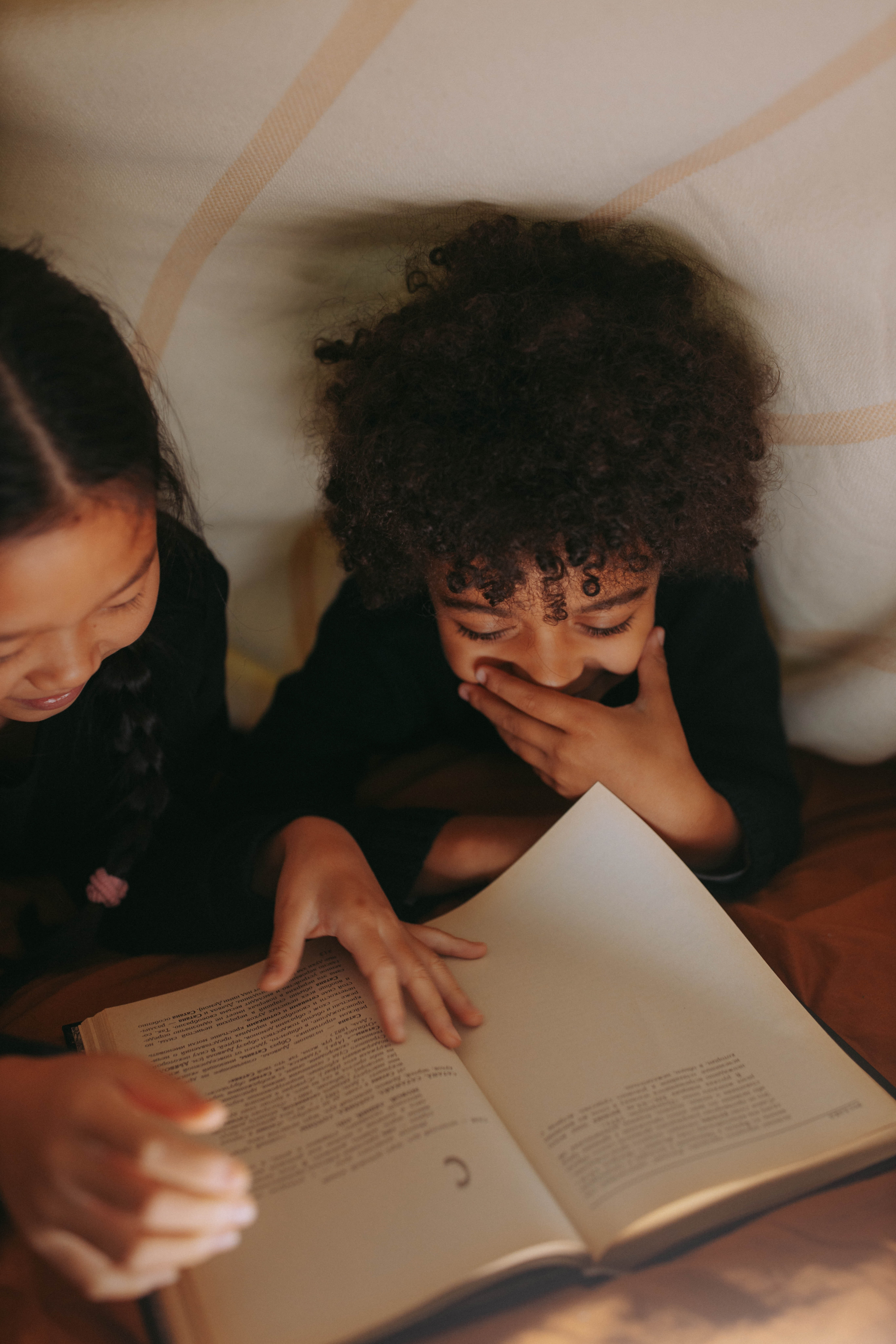 Two children reading in a blanket fort. One child is laughing.