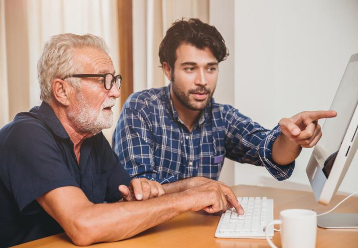 Young man helping older man with computer