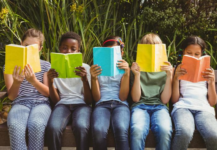 5 children holding up books and reading